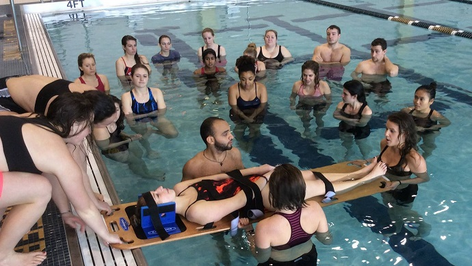 Students Practice Spineboarding in Swimming Pool