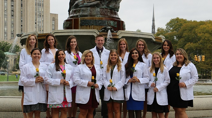 Students with White Coats standing in front of fountain on campus