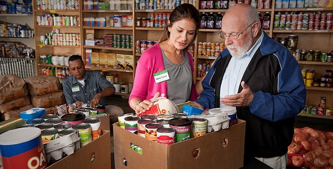 Student with older man filling box of food at food bank