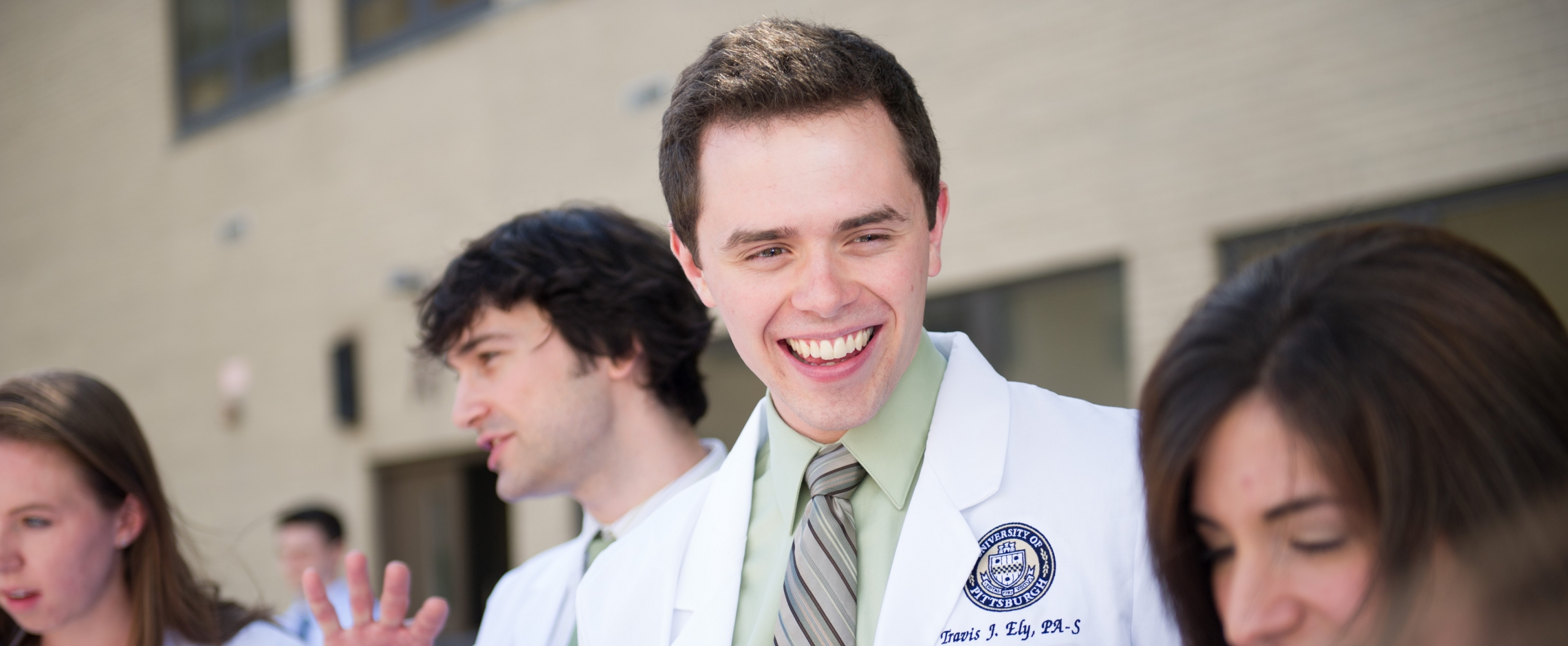 PA Student in white coat smiling