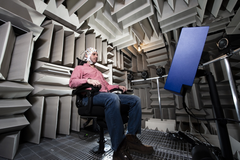 Participant seated in anechoic chamber wearing an EEG cap