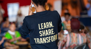 Girl with t-shirt that says learn, share, transform