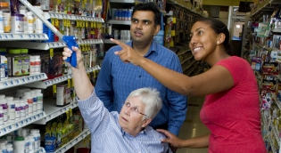 OT student and faculty help patient reach items safely on a shelf using assistive device