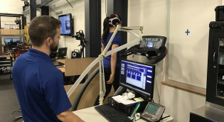 Researcher with participant on treadmill