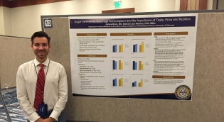 Student with Nutrition Research Poster