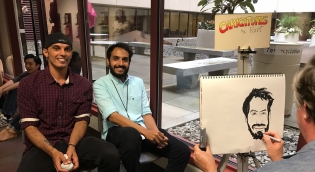 Students posing for caricature artist