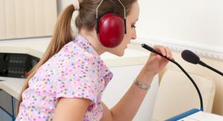 Student with headphones using testing equipment