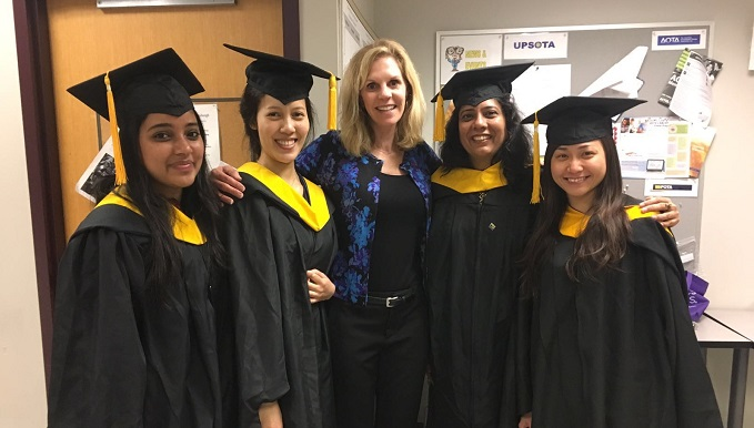 OT faculty member with students in caps and gowns