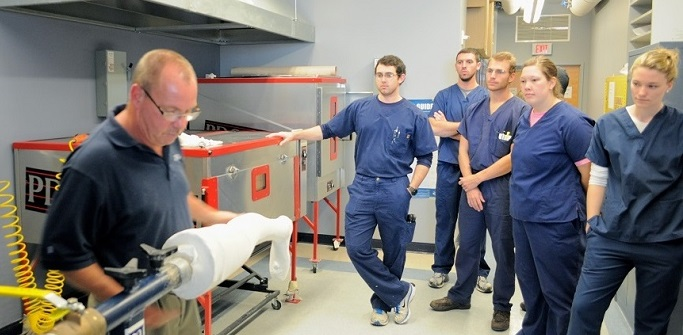 PO Students watching instructor in PO lab with equipment