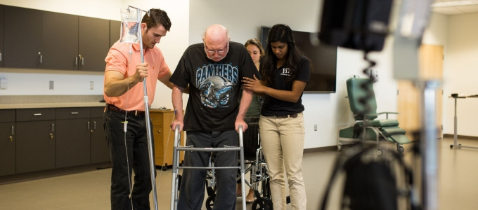 students helping patient model with walker