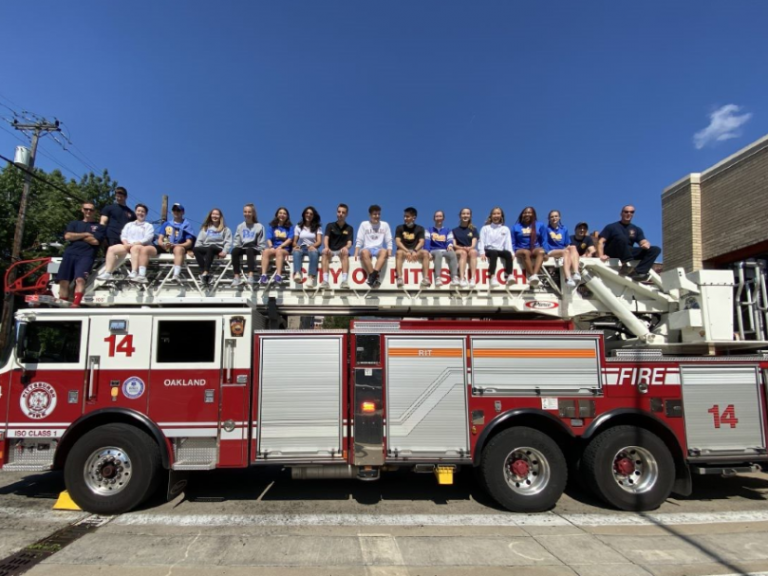 students and firefighters on a firetruck